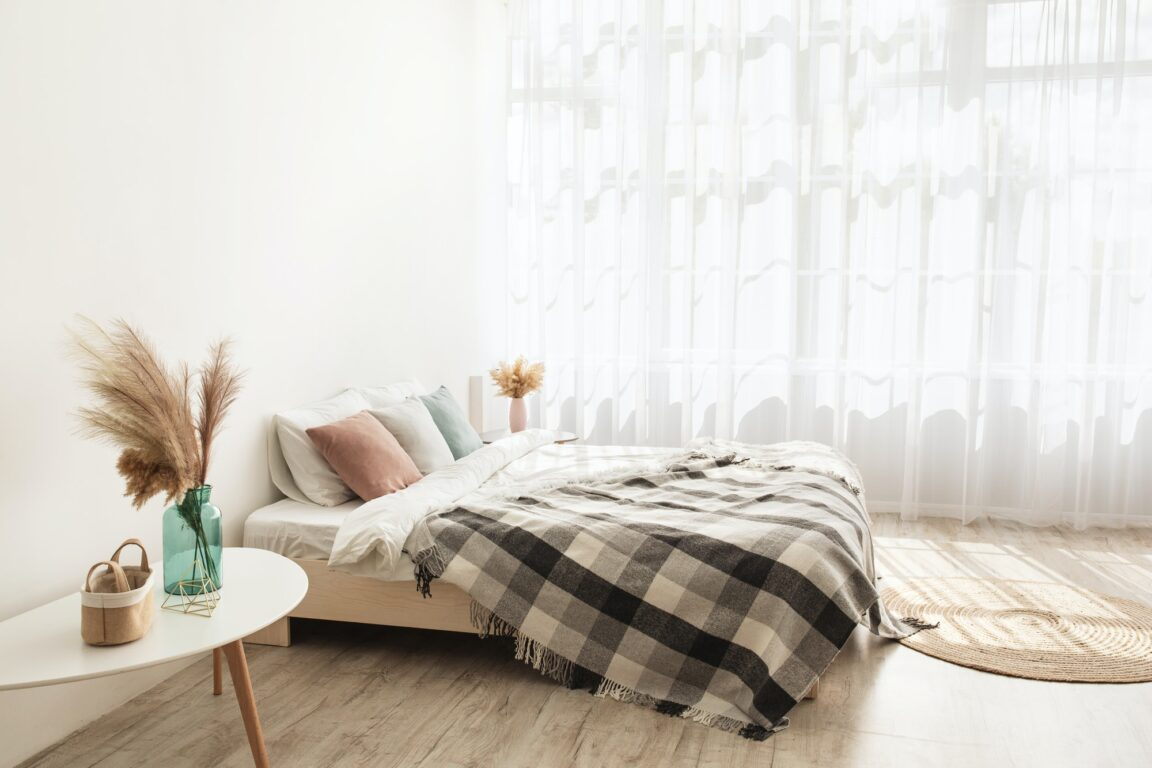 Light boho style and real estate design. Bed with pillows and blanket, carpet, tables with dry